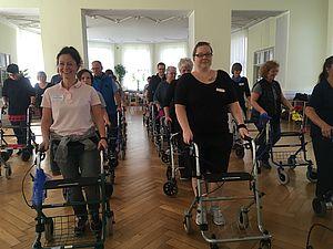 Veranstaltungsteilnehmende laufen mit Rollatoren durch den Raum