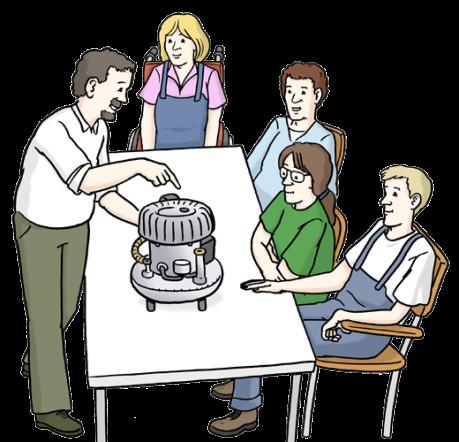 In einer Gruppe am Tisch wird von einem Mann ein Motor erklärt