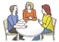 Teilnehmende sitzen am Tisch und diskutieren